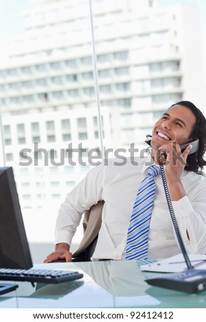 Portrait of a delighted businessman on the phone in his office