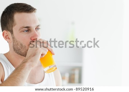 Portrait of a delighted man drinking orange juice in his kitchen - stock photo