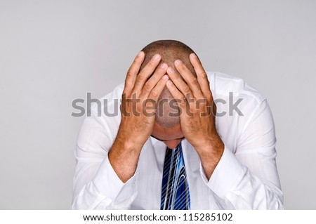 Portrait of a  depressed businessman holding head with hands