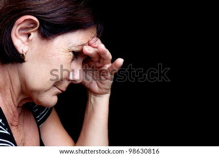 Portrait of a depressed older woman suffering from stress or a strong headache isolated on black - stock photo