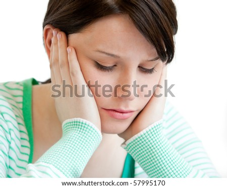 Portrait of a depressed teenager holding up her head on her hands against white background - stock photo