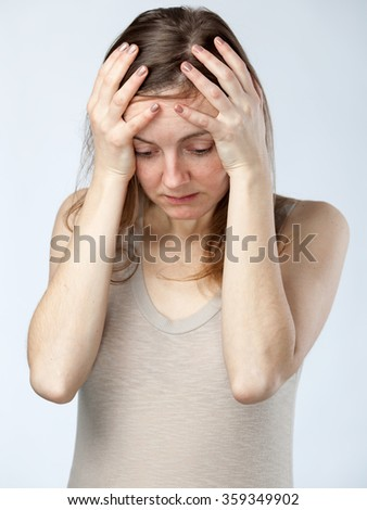 Portrait of a despaired woman in a beige shirt,  hands on the forehead , isolated on cold white background. Close up - stock photo