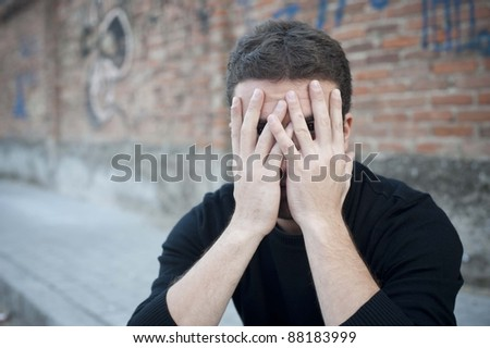 portrait of a desperate man in a urban street meaning loneliness - stock photo