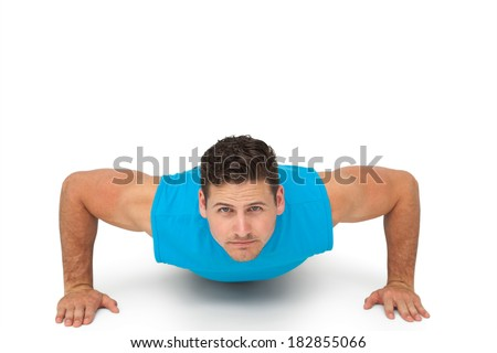 Portrait of a determined young man doing push ups over white background