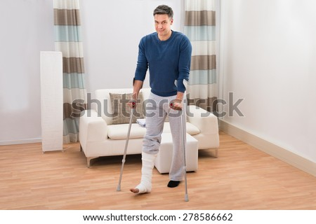 Portrait Of A Disabled Man Using Crutches For Walking At Home - stock photo