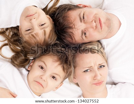 Portrait of a  displeased family having fun together lying on a bed at home - top view - stock photo