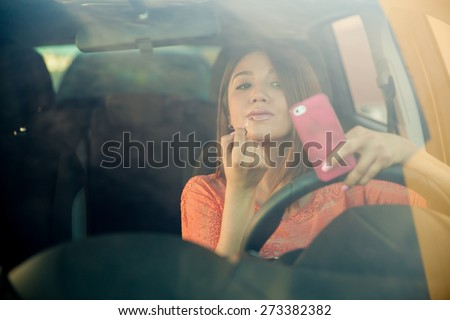 Portrait of a distracted young woman looking at her smartphone and putting some lipstick on while driving a car - stock photo