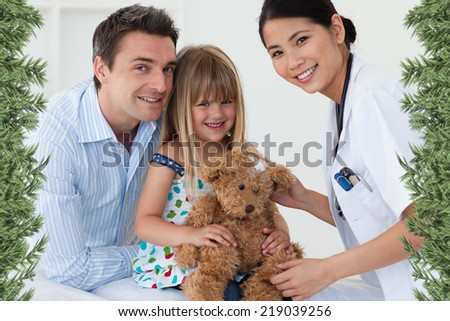 Portrait of a doctor and happy little girl examing a teddy bear against green fir branches - stock photo
