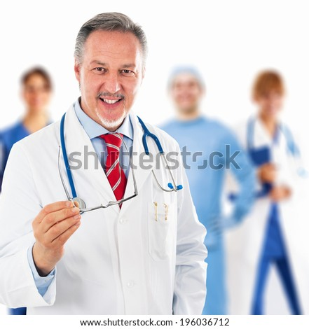 Portrait of a doctor in front of his team - stock photo