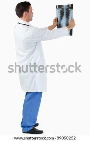 Portrait of a doctor looking at x-ray against a white background