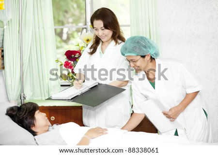 Portrait of a doctor with his co-workers talking with a patient - stock photo