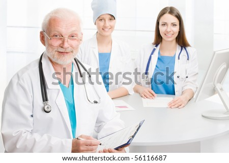 Portrait of a doctor with two co-workers sitting  in the background - stock photo