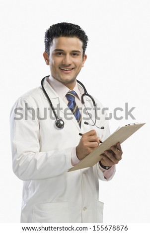 Portrait of a doctor writing on a clipboard