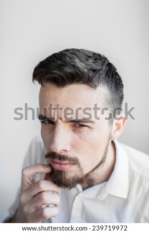Portrait of a doubtful pensive guy isolated on white. Portrait of suspicious young man, isolated on white background. - stock photo