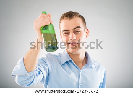 Portrait of a drunken young man holding bottle - stock photo