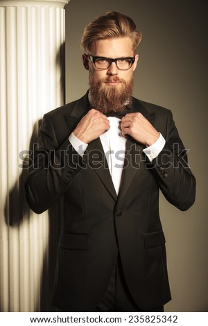 Portrait of a elegant business man fixing his bowtie while looking at the camera. - stock photo