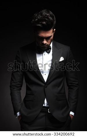 Portrait of a elegant young business man looking down while holding both hands in his pocket. - stock photo