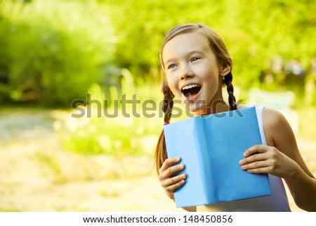 portrait of a emotional girl holding a book on green background - stock photo