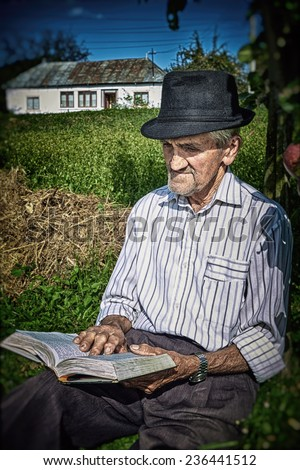 Portrait of a expressive old farmer reading leaning on an apple tree. - stock photo