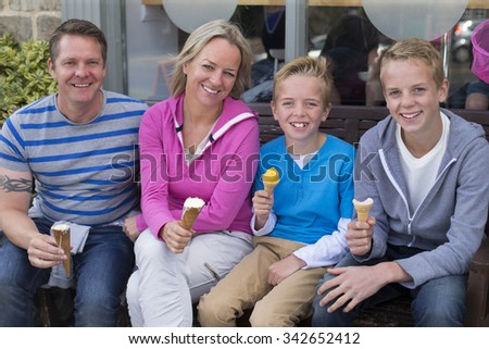 Portrait of a family enjoying ice cream outside of a shop. They are wearing casual clothing and smiling at the camera.  - stock photo