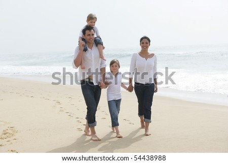 Portrait of a family having a walk by the edge of the sea - stock photo