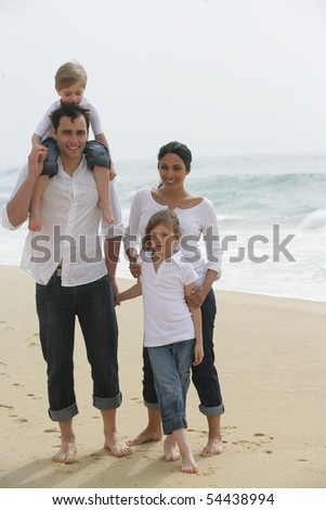 Portrait of a family having a walk by the edge of the sea