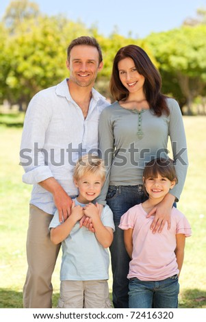 Portrait of a family in the park - stock photo