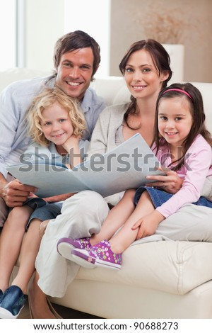 Portrait of a family looking at a photo album in a living room - stock photo