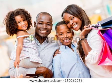 Portrait of a family shopping and looking very happy  - stock photo