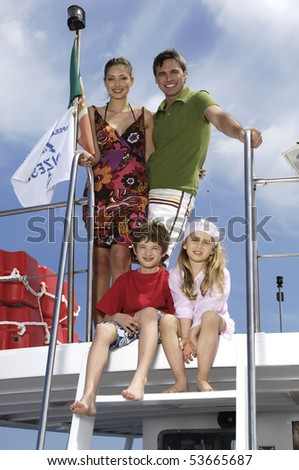 portrait of a family standing on a boat - stock photo