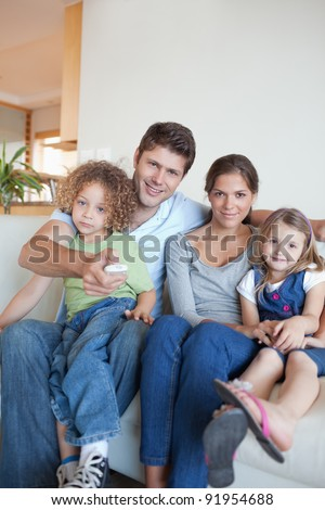 Portrait of a family watching TV together in their living room - stock photo