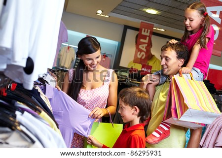 Portrait of a family with shopping bags choosing new clothes in the mall