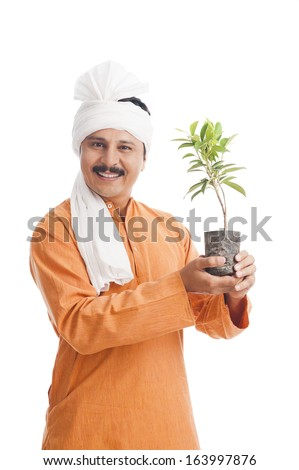 Portrait of a farmer holding a potted plant and smiling - stock photo