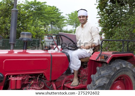 Portrait of a farmer with a laptop sitting on a tractor - stock photo