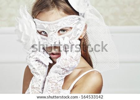 Portrait of a fashion girl wearing wedding dress and venetian mask - stock photo