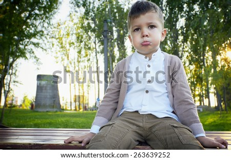 Portrait of a fashion 3 years old handsome boy, upset. Outdoor picture. - stock photo