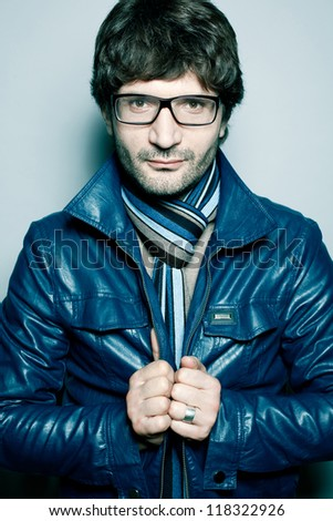 Portrait of a fashionable handsome man in blue jacket with striped scarf over light blue background. studio shot - stock photo