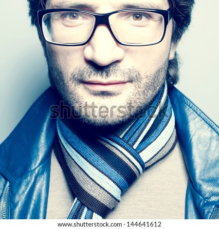 Portrait of a fashionable handsome man in blue jacket with striped scarf over light blue background. Hipster style. Close up. studio shot - stock photo