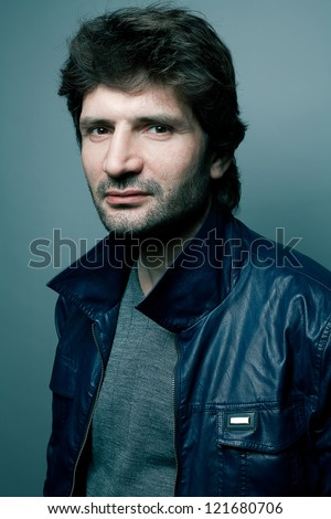 Portrait of a fashionable handsome man in gray sweater (pullover) and blue leather jacket over blue (green) background. studio shot - stock photo