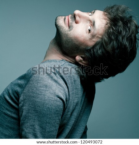 Portrait of a fashionable handsome model in gray sweater (pullover) over blue (green) background with his chin up. Studio shot - stock photo
