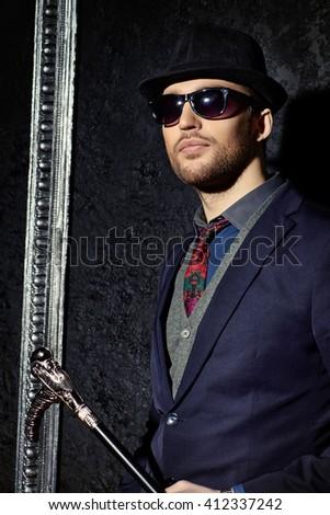 Portrait of a fashionable male model wearing elegant suit. Studio shot. - stock photo