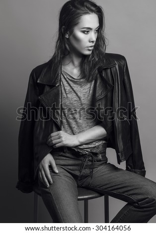 Portrait of a fashionable model with natural make up and perfect skin, dressed in men's jeans, grey shirt, black jacket and sneakers.Studio shot. High fashion look.Monochrome (black and white)  photo - stock photo