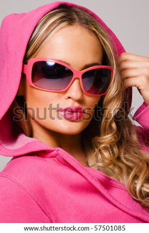 Portrait of a fashionable woman in pink cowl and sunglasses - stock photo