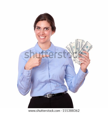 Portrait of a fashionable young woman in blue blouse smiling while pointing to cash money, on isolated white background.