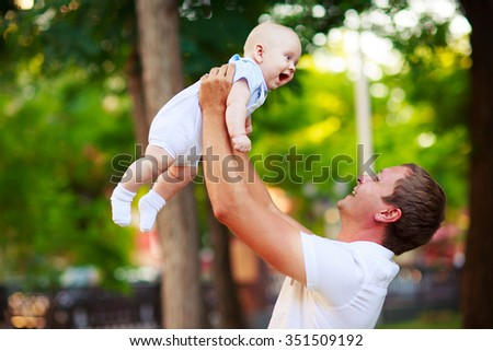 Portrait of a father and baby outdoors - stock photo