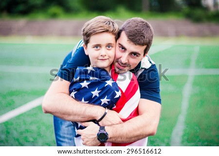 Portrait of a father and son holding American flag. Shallow depth of field - stock photo