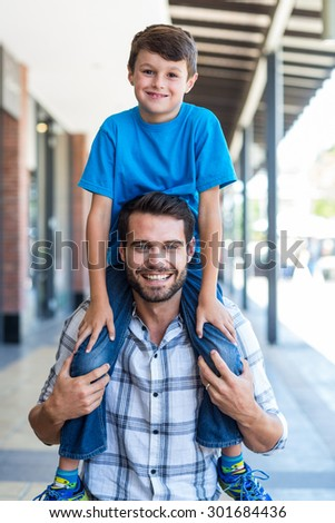 Portrait of a father and son piggybacking at the mall - stock photo