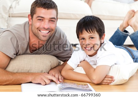 Portrait of a father and son reading a book together on the floor at home - stock photo