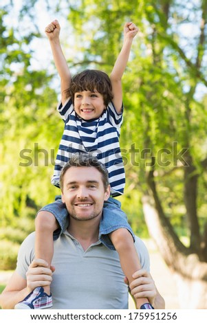 Portrait of a father carrying a happy son on shoulders at the park - stock photo