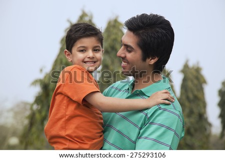 Portrait of a father holding his son